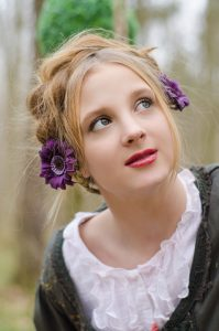 Portrait of a beautiful young girl with decorative flowers in h